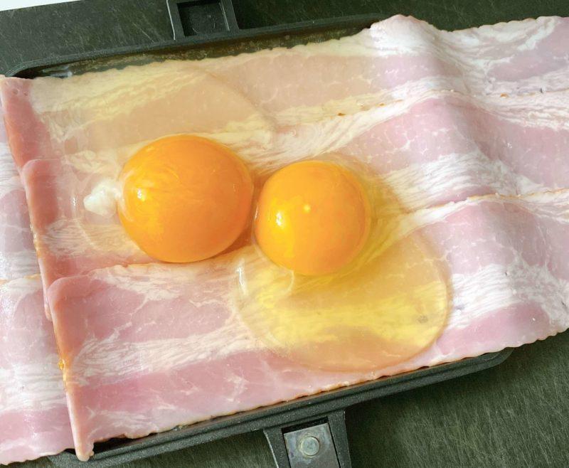包み焼きベーコンエッグの作り方③|ベーコンの上に卵を2つ割ってのせ、塩こしょう少々、チーズをかける